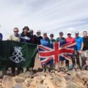 The team holding up our flags at another summit