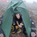 Sgt Dave Titcombe testing the tent weighed down with  rocks as pegging in the mountains often tricky.