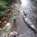 The group lining their canoes and equipment up the river to their campsite