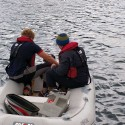 The second mate and watch leader attempt to repair a broken outboard.